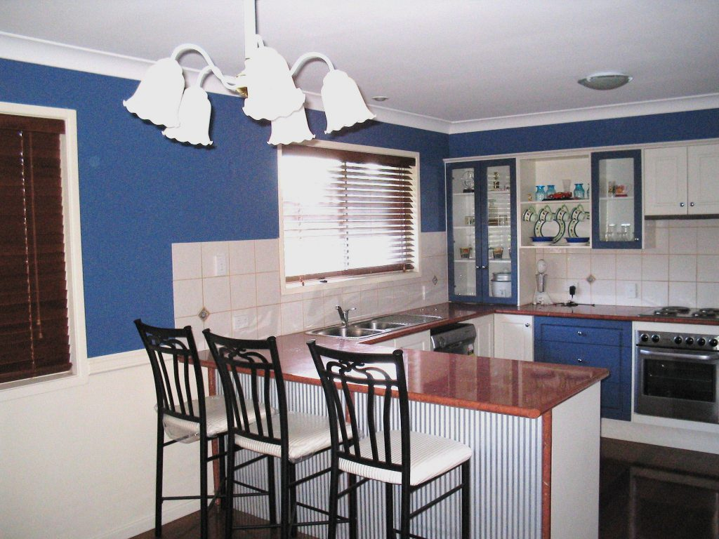 Image is of a the same patterned door kitchen done with two colors (deep blue and antique white) and gloss laminate bench top.