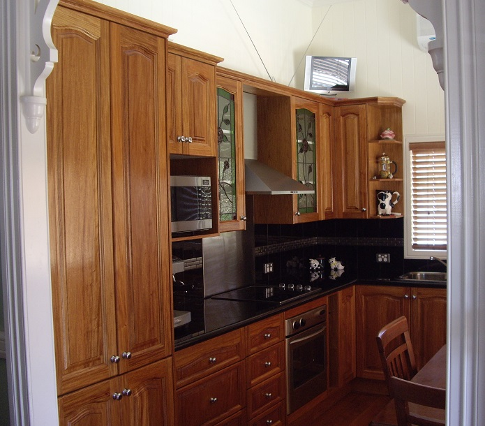 This image is of  a rosewood arched door kitchen with a black granite bench top and a black tiles splash back with colonial timber capping.