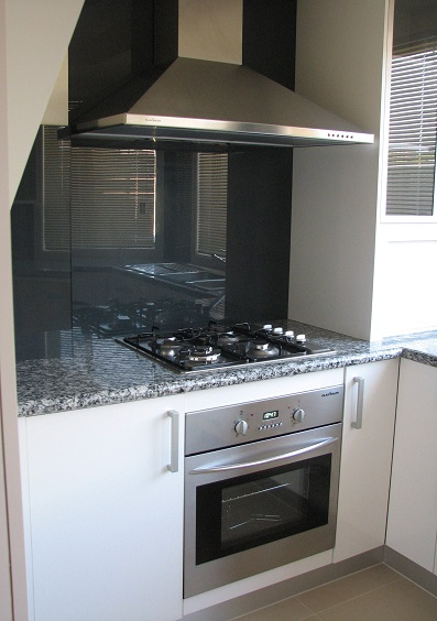 A second image of the white gloss melamine door kitchen with a gloss blackish-granite laminate bench top.