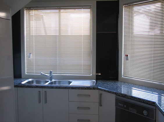 The image is of a white gloss melamine door kitchen with a gloss blackish-granite laminate bench top.