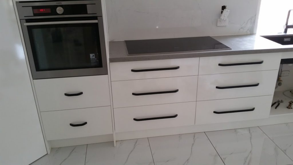 The image is showing lots of melamine faced white gloss soft close drawers with a laminate bench top.