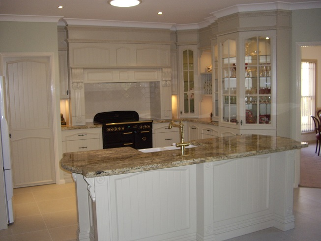 Image is of a colonial kitchen with all the charms of a rich and opulent lifestyle of a past era. Colonial 2 PAC doors with granite bench top and lots of glass display cabinets.