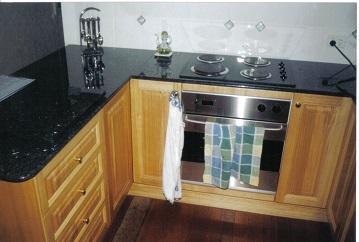 The image again displays Tasmanian Oak doors with black granite bench top with a light tiled splash back.