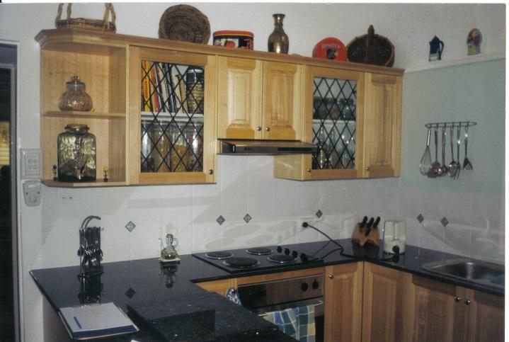 Image displays Tasmanian Oak doors with black granite bench top with a light tiled splash back.