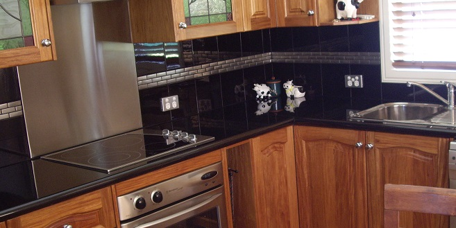 Kitchen image displaying granite bench top over Rosewood timber doors with an arch top in the door pattern.