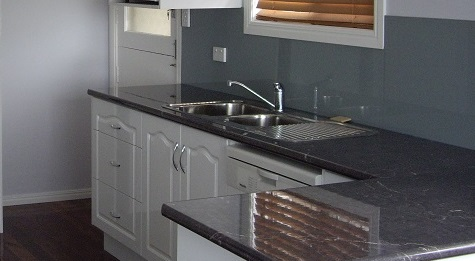 The Kitchen image shows a granite design gloss laminate bench top with an arch top 2 pac door.