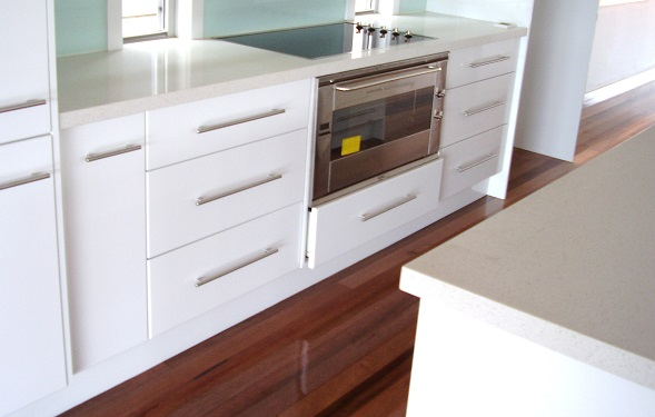 The kitchen image displays a stone bench top over a flat panel 2 PAC door with  color of gloss white.